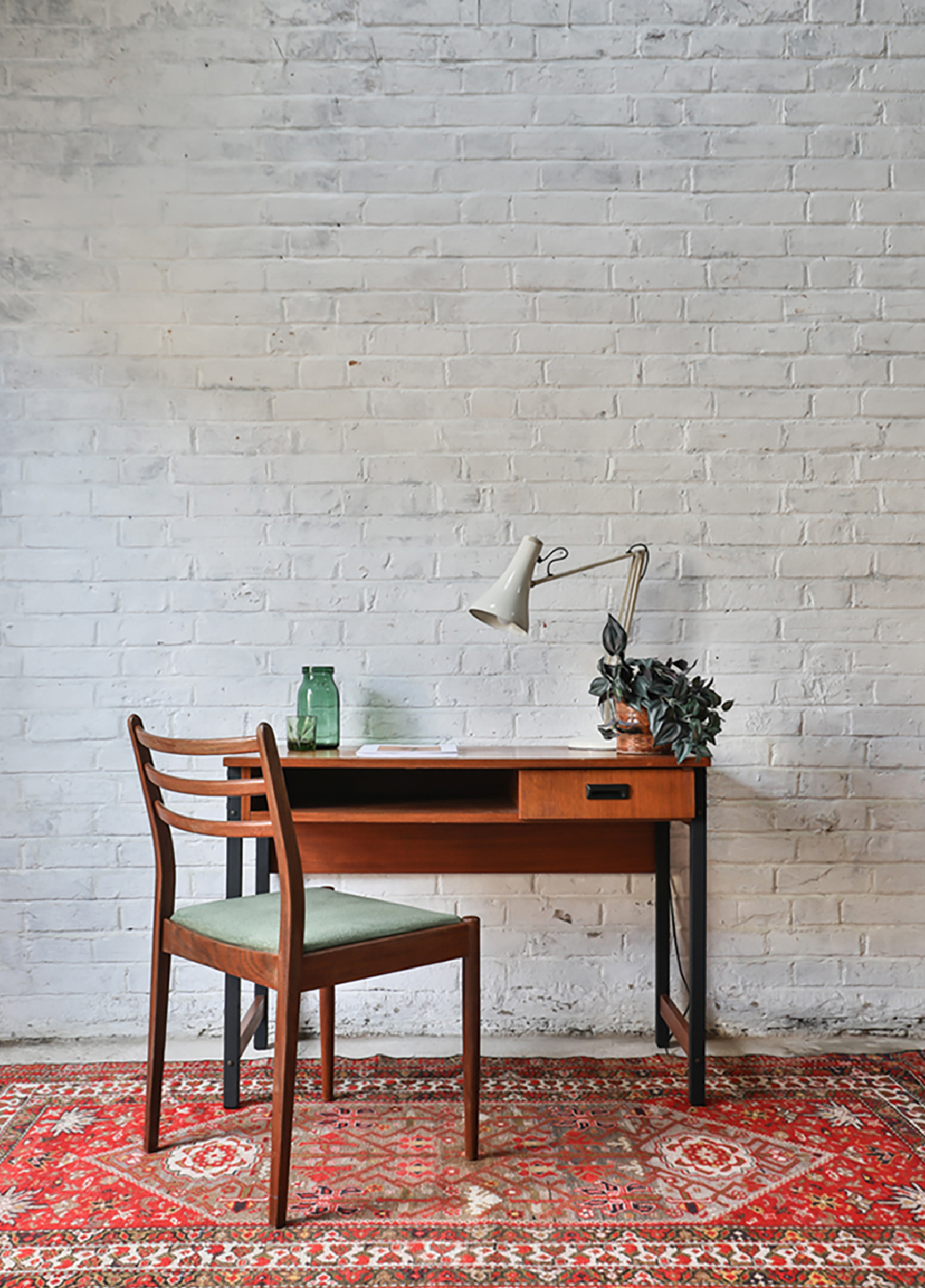 A vintage desk and chair on a rug