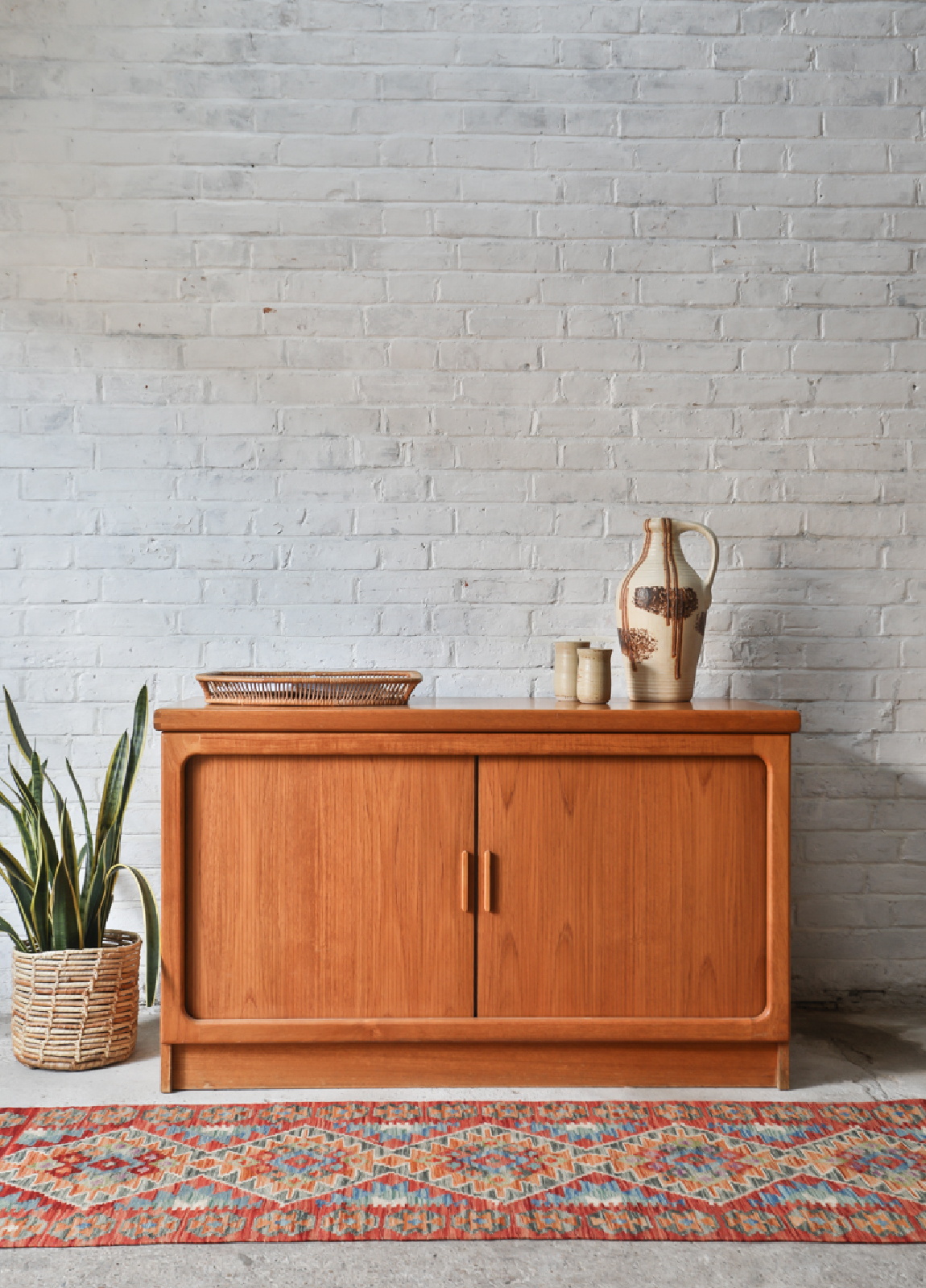 A mid-century cabinet and pottery